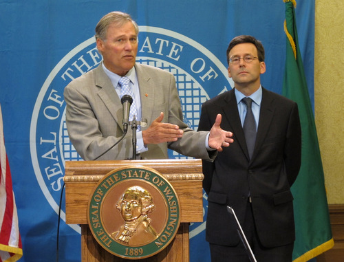 Washington state Gov. Jay Inslee, left, is joined by state Attorney General Bob Ferguson as he talks to the media in Olympia, Wash. about the federal government's announcement that it will not sue to stop Washington and Colorado from taxing and regulating recreational marijuana for adults, on Thursday, Aug. 29, 2013. Last fall, voters made both states the first in the country to legalize the sale of marijuana to adults over 21 at state-licensed stores. The states are creating rules for the system, with sales expected to begin early next year. (AP Photo/Rachel La Corte)
