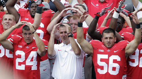 """Ohio State head coach Urban Meyer, center, sings """"Carmen Ohio"""" with his players  after their 40-20 win over Buffalo in an NCAA college football game Saturday, Aug. 31, 2013, in Columbus, Ohio. (AP Photo/Jay LaPrete)"""