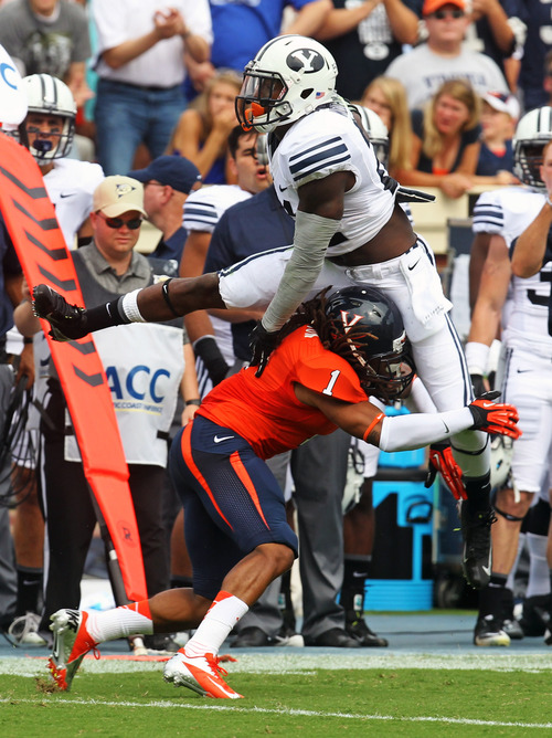 Brigham Young running back Jamaal Williams (21) attempts to leap over Virginia cornerback Demetrious Nicholson (1) the first half of an NCAA college football game, Saturday, Aug. 31, 2013 in Charlottesville, Va. (AP Photo/The Daily Progress, Andrew Shurtleff)