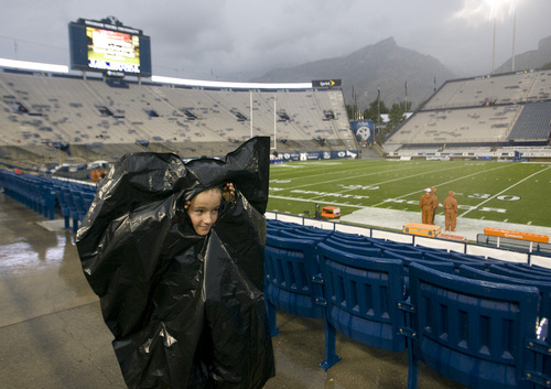 Rick Egan  | The Salt Lake Tribune   Enoch Frazier, 10, Alpine peeks out of a garbage bag, as the game was delated, and fans were told to seek cover from the rain and lightening, as a huge rainstorm hit Lavell Edwards stadium, an hour before game time, as BYU prepared to face the University of Texas, Saturday, September 7, 2013.