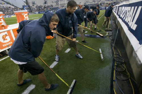 Rick Egan  | The Salt Lake Tribune   BYU grounds crews squeegee water form the field during the rain delay, as a huge rainstorm hit Lavell Edwards stadium, an hour before game time, as BYU prepared to face the University of Texas, Saturday, September 7, 2013.