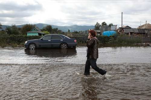A local resident talking on a phone, walks in a flooded street,  in Mendeleyevo on the outskirts of Komsomolsk-on-Amur,  Russian Far East, Saturday, Sept. 7, 2013. Flooding in Russia's Far East, the worst since records began over a century ago, continued to affect residents across the region on Saturday. (AP Photo/ Vladimir Barsukov)