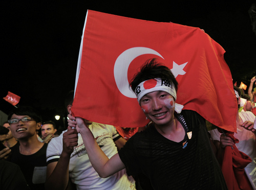 A Japanese tourist waves a Turkish national flag in  Sultan Ahmed Square in Istanbul, Turkey, as he celebrates Tokyo's win  Saturday, Sept. 7, 2013. The International Olympic Committee voted  in Buenos Aires, Argentina, late Saturday for Tokyo against Istanbul and Madrid to host  the 2020 Summer Olympics,.(AP Photo)