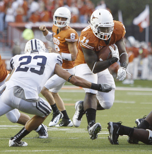 Texas' Cody Johnson (11) tries to avoid BYU defender Travis Uale (23) during the first quarter of an NCAA college football game, Saturday, Sept. 10, 2011, in Austin, Texas. (AP Photo/Eric Gay)