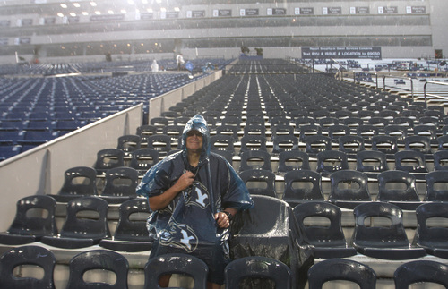 Rick Egan  | The Salt Lake Tribune   Lynn Tuttle, Orem, rides out the rainstorm in his seat 30 minutes before the game was supposed to start, as BYU prepared to face the University of Texas, at Lavell Edwards Stadium, Saturday, September 7, 2013. The game was delayed due to lightening.