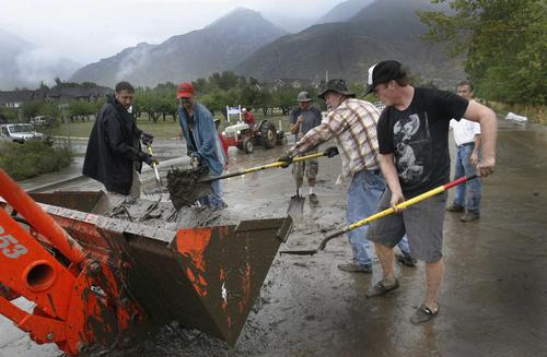 Scott Sommerdorf   |  The Salt Lake Tribune Volunteers help remove mud after mudslides in Alpine, Sunday, September 8, 2013.