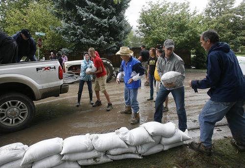 Scott Sommerdorf   |  The Salt Lake Tribune Volunteers place sandbags at the intersection of Alpine Blvd., and 860 East after mudslides in Alpine, Sunday, September 8, 2013.