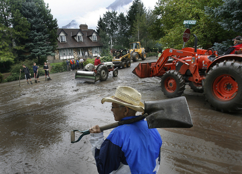 Scott Sommerdorf   |  The Salt Lake Tribune Volunteers including John Lilly help clean up mud that flowed down Alpine Blvd at the intersection of Alpine and 860 East after mudslides in Alpine, Sunday, September 8, 2013.