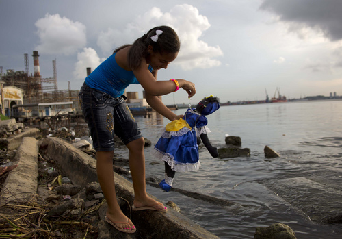 A girl with a doll representing the Virgin of Regla prays at sea before a procession in honor of the Virgin in the town of Regla, across the bay from Havana, Cuba, Saturday, Sept. 7, 2013. The black Madonna is honored on the same day as Cuba's patron saint, the Virgin of Charity, both of which are also recognized as powerful deities in the African-influenced religion of Santeria. (AP Photo/Ramon Espinosa)