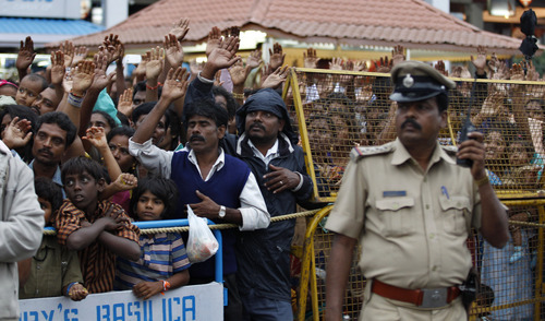 An Indian police official stands guard as worshippers react to a priest as they participate in Mary's Feast outside the St. Mary's Basilica, the oldest church of Bangalore, India, Sunday, Sept. 8, 2013. (AP Photo/Aijaz Rahi)