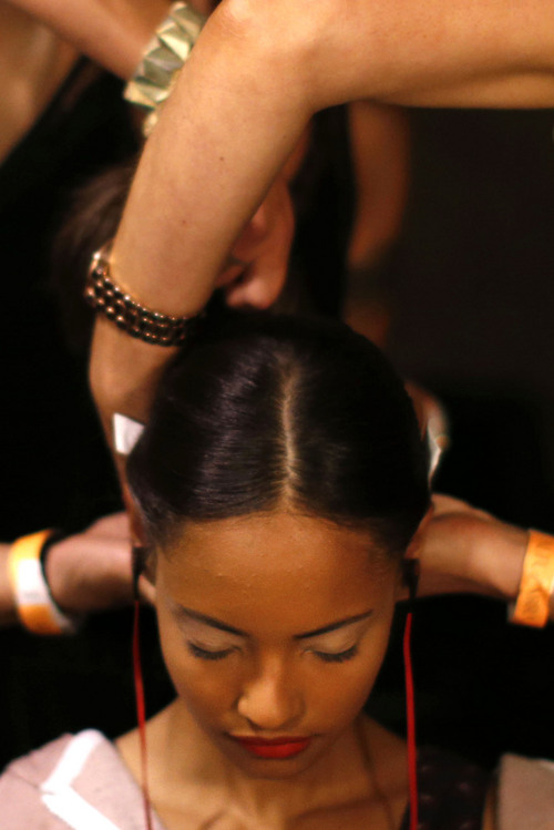 A tangle of arms works to style the hair of model Malaika Firth, of Britain, backstage before the Altuzarra Spring 2014 collection show during Fashion Week, Saturday, Sept. 7, 2013, in New York. (AP Photo/Jason DeCrow)