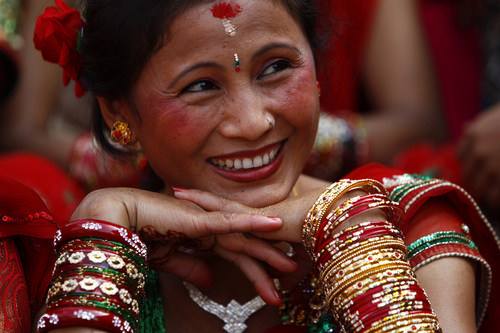 A Nepalese woman reacts as he watches her friends dance at the Pashupatinath Hindu temple during Teej festival celebrations in Katmandu, Nepal, Sunday, Sept. 8, 2013. During the festival, married Hindu women observe day-long fast and pray for their husbands and a happy married life while those unmarried pray for a good husband. (AP Photo/Niranjan Shrestha)