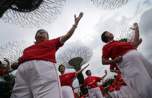 Elderly women practice Tai Chi, a Chinese form of meditative exercise, Sunday, Sept. 8, 2013, at the Gardens by the Bay in Sinagpore. The city-state's government ministries often organize events to boost morale and promote a healthy life-style for its aging population. (AP Photo/Wong Maye-E)
