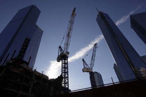 Construction cranes work between Four World Trade Center, left, and One World Trade Center, right, Sunday, Sept. 8, 2013 in New York. Twelve years after terrorists destroyed the old World Trade Center, the new World Trade Center is becoming a reality, with a museum commemorating the attacks and two office towers where thousands of people will work set to open within the next year. (AP Photo/Mark Lennihan)