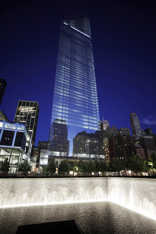 Four World Trade Center, center, rises above waterfalls at the National September 11 Memorial and Museum, Sunday, Sept. 8, 2013 in New York. Twelve years after terrorists destroyed the old World Trade Center, the new World Trade Center is becoming a reality, with a museum commemorating the attacks and two office towers where thousands of people will work set to open within the next year. (AP Photo/Mark Lennihan)
