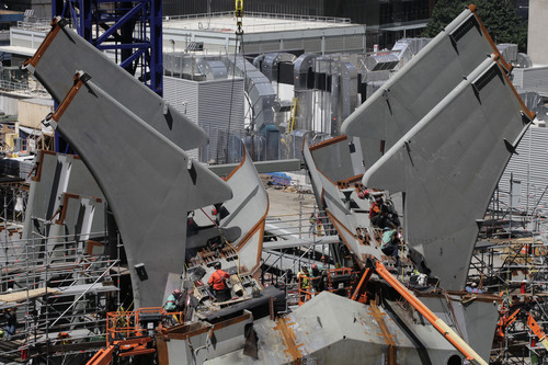 In this August 15, 2013 photo, workers install trusses for the World Trade Center transportation hub in New York. Twelve years after terrorists destroyed the old World Trade Center, the new World Trade Center is becoming a reality, with a museum commemorating the attacks and two office towers where thousands of people will work set to open within the next year. (AP Photo/Mark Lennihan)