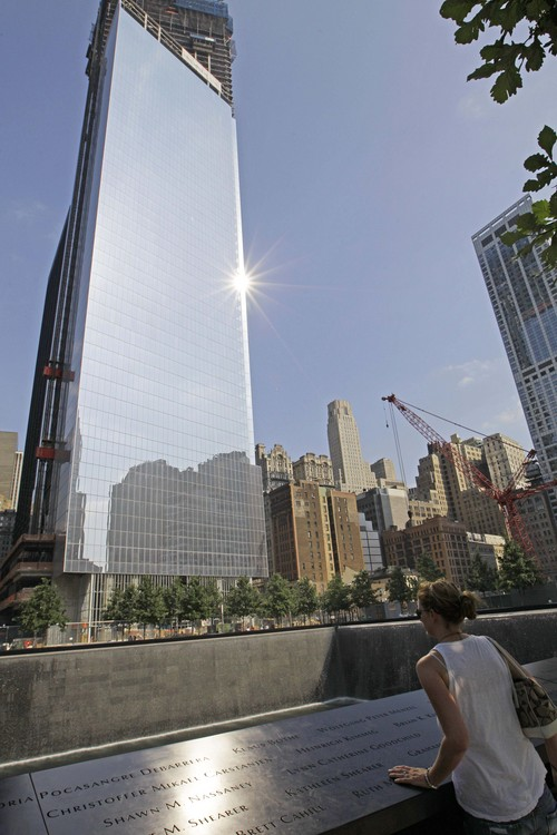 FILE - In this June 21, 2012 photo, the sun reflects off 4 World Trade Center as a woman looks into the one of the reflecting pools at the 9/11 Memorial in New York.  Developers expect the 72-story, 977-foot building at the southeast corner of the site to open in November 2013. Its main tenant will be the Port Authority, the bi-state agency that owns the trade center site and that lost its home when the twin towers fell. (AP Photo/Kathy Willens)