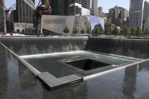 FILE - In this Aug. 17, 2011, file photo, the National September 11 Memorial and Museum is seen in the background as water flows in the south pool of the World Trade Center Memorial in New York. Twelve years after terrorists destroyed the old World Trade Center, the new World Trade Center is becoming a reality, with a museum commemorating the attacks and two office towers where thousands of people will work set to open within the next year. (AP Photo/Mary Altaffer, File)