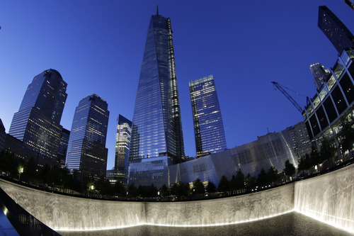 In this image made with a fisheye lens, One World Trade Center, center, rises above waterfalls at the National September 11 Memorial and Museum, Sunday, Sept. 8, 2013, in New York. Twelve years after terrorists destroyed the old World Trade Center, the new World Trade Center is becoming a reality, with a museum commemorating the attacks and two office towers where thousands of people will work set to open within the next year. (AP Photo/Mark Lennihan)