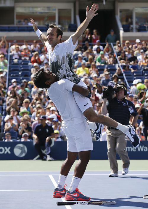 Leander Paes, left, lifts Radek Stepanek, of the Czech Republic, after beating Alexander Peya of Austria and Bruno Soares of Brazil in the men's doubles final of the 2013 U.S. Open tennis tournament, Sunday, Sept. 8, 2013, in New York. (AP Photo/Darron Cummings)