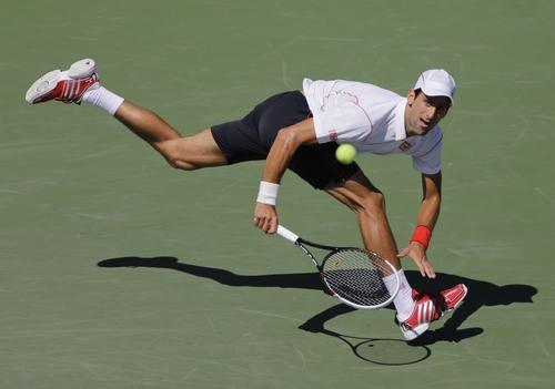 Novak Djokovic, of Serbia, returns a shot against Stanislas Wawrinka, of Switzerland, during the semifinals of the 2013 U.S. Open tennis tournament, Saturday, Sept. 7, 2013, in New York. (AP Photo/Mike Groll)