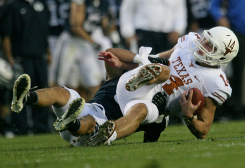 Rick Egan  | The Salt Lake Tribune   Texas Longhorns quarterback David Ash (14) gets sacked by Brigham Young Cougars linebacker Alani Fua (5) in the Cougars 40-21 win over the University of Texas at Lavell Edwards stadium, Saturday, September 7, 2013.