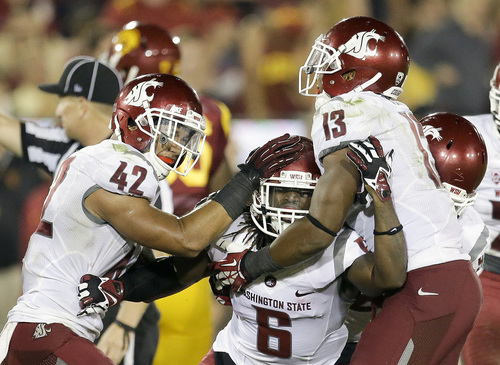 Washington State cornerback Damante Horton, middle, celebrates his interception with teammates Cyrus Coen, left, and Darryl Monroe during the second half of an NCAA college football game against Southern California in Los Angeles, Saturday, Sept. 7, 2013. (AP Photo/Chris Carlson)