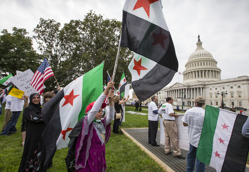 Demonstrators opposed to the government of Syrian President Bashar Assad gather on the lawn of the Capitol in Washington, Monday, Sept. 9, 2013, as Congress returns to work from August recess. The protesters are waving the flag of the Syrian opposition movement.  (AP Photo/J. Scott Applewhite)