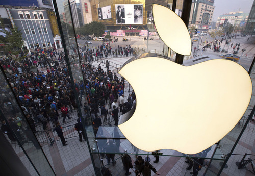 "FILE - In this Oct. 20, 2012 photo, people line up to enter a newly-opened Apple Store in Wangfujing shopping district in Beijing. Apple is unveiling the latest version of its iPhone, possibly named the ""iPhone 5S,"" on Sept. 10, 2013. It's rumored that it will come in a new gold or ""champagne"" color as well as have a faster processor, better camera and possibly a fingerprint sensor for security. Apple also is poised to introduce a new low-cost version of the iPhone, possibly called the ""iPhone 5C,"" that will be similar in specifications to this year's iPhone 5 but with a cheaper plastic backing that also will come in other colors. But what about other Apple products? It's more than likely that the Cupertino, Calif., company will introduce more from its stable of products than just the next iPhone and a new low-cost phone. (AP Photo/Andy Wong, File)"