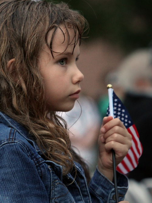 Rick Egan  | The Salt Lake Tribune   Six-year-old Trinity Fullmer holds a flag as she listens to the speakers, during the 911ceremony in front of the Sandy City Hall, Wednesday, September 11, 2013.