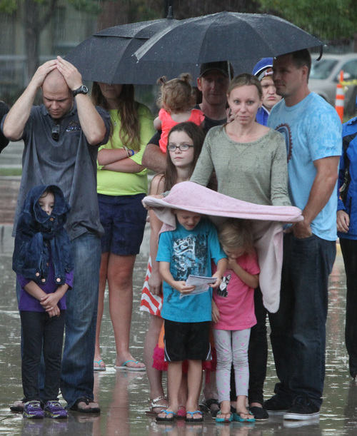 Rick Egan  | The Salt Lake Tribune   Rain didn't chase many people away, as it continutes to fall during the 911ceremony in front of the Sandy City Hall, Wednesday, September 11, 2013.