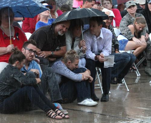 Rick Egan  | The Salt Lake Tribune   Members of Derek Johnson's family brave the rain, during the 911ceremony in front of the Sandy City Hall, Wednesday, September 11, 2013.