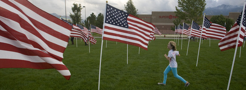 Rick Egan  | The Salt Lake Tribune   Leah Hurt, 8, runs through the flags in the healing field, before the 911ceremony in front of the Sandy City Hall, Wednesday, September 11, 2013.