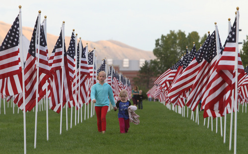 Rick Egan  | The Salt Lake Tribune   Olivia Housley, 11, walks through the flags in the healing field with her sister Kaisa, 6, before the 911ceremony in front of the Sandy City Hall, Wednesday, September 11, 2013.