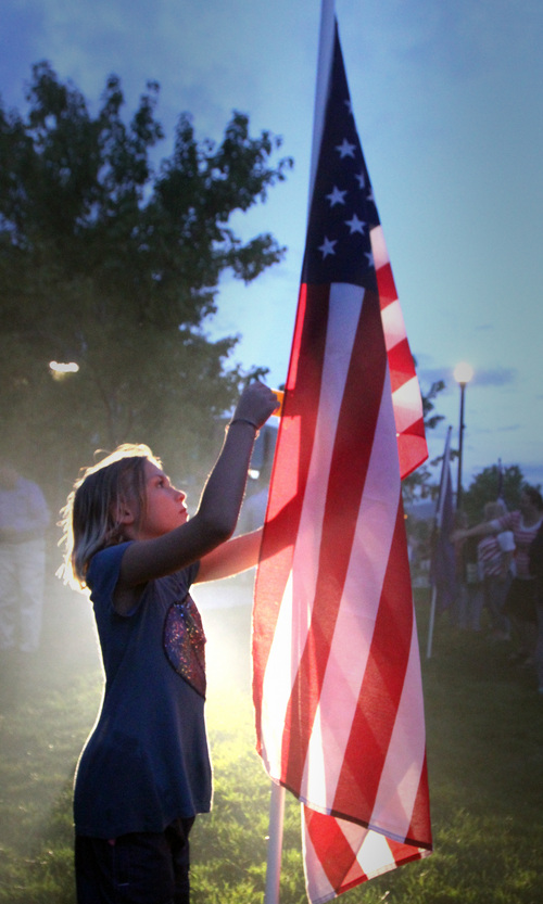 Rick Egan  | The Salt Lake Tribune   Erika Marble,9, checks the names on the flags in front of the Sandy City Hall, after the 911ceremony in Wednesday, September 11, 2013.
