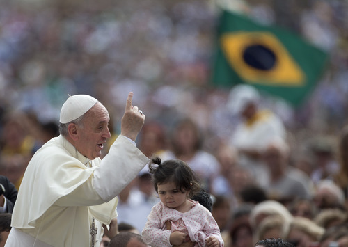 """Pope Francis arrives for his weekly general audience as a Brazilian flag is being waved in background, in St. Peter square at the Vatican, Wednesday Sept. 11, 2013. Pope Francis has gotten his first Italian byline with a letter published on the front page of the Rome-based daily La Repubblica. The pope responded to a pair of letters from the daily's founder and long-time editor Eugenio Scalfari, who posed a series of theological questions as a non-believer to the pontiff in the paper over the summer. Francis responded """"God forgives those who follow their conscience"""" to 89-year-old Scalfari's question of whether someone without faith who commits a sin would be forgiven by the Christian God. In his letter, printed across three pages, Francis said """"it is time for an open dialogue on faith without any preconceived notions."""" (AP Photo/Alessandra Tarantino)"""