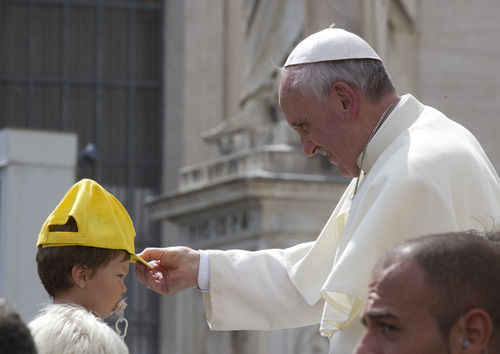 Pope Francis adjusts a hat on a child's head as he leaves after his weekly general audience in St. Peter's Square at the Vatican, Wednesday, Sept. 11, 2013. During open-air general audiences the pontiff is driven through the crowd before delivering his message, which is translated in several languages, to attendees from square beneath St. Peter's Basilica. (AP Photo/Alessandra Tarantino)