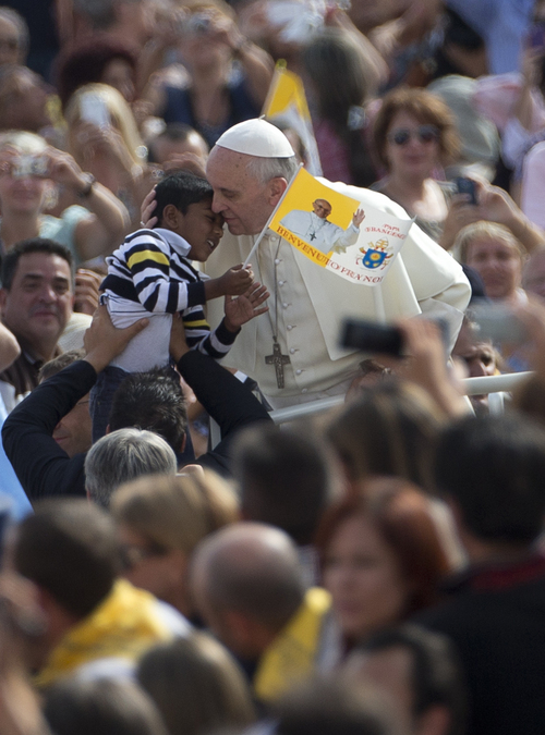 Pope Francis kisses a child held out to him as he is driven through the crowd during his weekly general audience in St. Peter's Square at the Vatican, Wednesday Sept. 11, 2013. During open-air general audiences the pontiff is driven through the crowd before delivering his message to attendees from the square in front of St. Peter's Basilica. (AP Photo/Alessandra Tarantino)