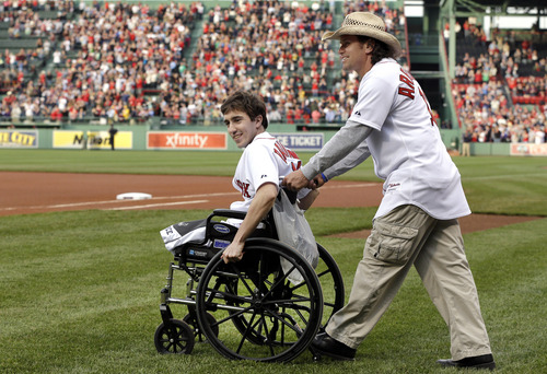 """FILE - Boston Marathon bombing survivor Jeff Bauman, left, is wheeled out by Carlos Arredondo, the man who helped save his life, to throw out the ceremonial first pitch at Fenway Park in a Tuesday, May 28, 2013 file photo, prior to a baseball game between the Boston Red Sox and the Philadelphia Phillies, in Boston. Bauman is working on a memoir with Grand Central Publishing to be titled  """"Stronger,"""" scheduled to come out in April. Grand Central announced Wednesday, Sept. 4, 2013 that the book would focus on Bauman's experiences during and after the bombings. (AP Photo/Elise Amendola, File)"""
