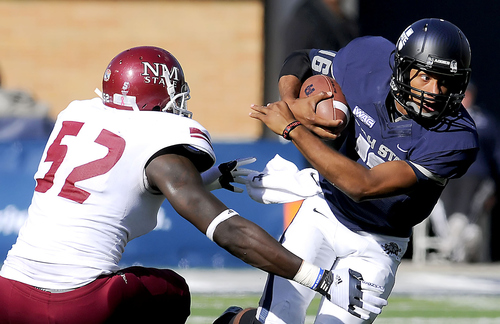 Utah State quarterback Chuckie Keeton (16) carries the ball as New Mexico State defensive lineman Donte Savage defends during an NCAA college football game on Saturday, Oct. 20, 2012, in Logan, Utah. (AP Photo/The Herald Journal, Eli Lucero)