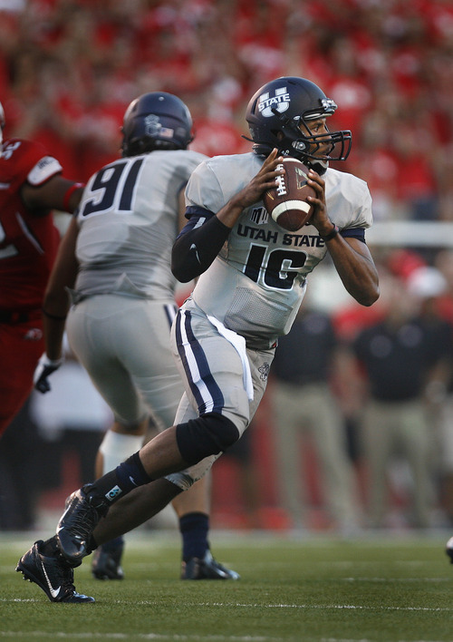 Scott Sommerdorf   |  The Salt Lake Tribune Utah State QB Chuckie Keeton rolls out during late first half play. USU held a 17-14 halftime lead over Utah, Thursday, August 29, 2013.