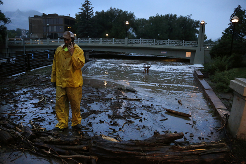 A city worker talks on his phone while surveying high water levels on Boulder Creek following overnight flash flooding in downtown Boulder, Colo., Thursday, Sept 12, 2013. Flash flooding in Colorado has left two people dead and the widespread high waters are keeping search and rescue teams from reaching stranded residents and motorists in Boulder and nearby mountain communities as heavy rains hammered northern Colorado. (AP Photo/Brennan Linsley)