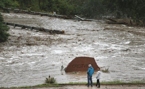 Local residents look over a road washed out by a torrent of water following overnight flash flooding near Left Hand Canyon, south of Lyons, Colo., Thursday, Sept 12, 2013. The widespread high waters are keeping search and rescue teams from reaching stranded residents in Lyons and nearby mountain communities as heavy rains hammered northern Colorado. (AP Photo/Brennan Linsley)