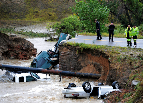 """Officials investigate the scene of a road collapse at Highway 287 and Dillon at the Broomfield/Lafayette border, Colo., that sent three vehicles into the water after flash flooding on Thursday, Sept. 12, 2013. The National Weather Service has warned of an """"extremely dangerous and life-threatening situation"""" throughout the region. (AP Photo/Daily Camera, Cliff Grassmick)"""