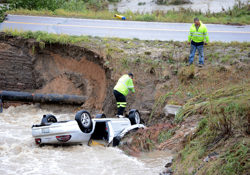 """A bridge collapse on a business access road at Highway 287 and Dillon Road at the Broomfield/Lafayette border, Colo., after flash flooding causes 3 cars to fall in the creek on Thursday, Sept. 12, 2013. The National Weather Service has warned of an """"extremely dangerous and life-threatening situation"""" throughout the region. (AP Photo/Daily Camera, Cliff Grassmick) NO SALES NO MAGS; NO TV;"""