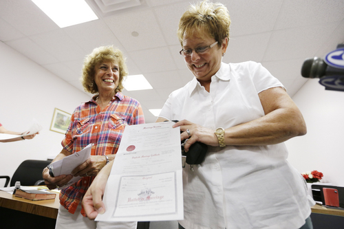 FILE - In this July 24, 2013 file photo Ellen Toplin, right, and Charlene Kurland show their new marriage license at a Montgomery County office despite a state law banning such unions, in Norristown, Pa. On Thursday, Sept. 12, 2013, Commonwealth Court Judge Dan Pellegrini ordered Montgomery County Register of Wills D. Bruce Hanes to stop issuing marriage licenses to same-sex couples. The judge said Hanes did not have the power to decide on his own whether Pennsylvania's same-sex marriage ban violates the state constitution. It was not immediately clear what the decision would mean to those who have already received a license. (AP Photo/Matt Rourke, File)