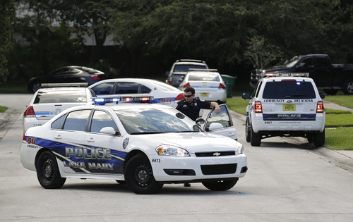 Police cars block the street at the scene of a domestic incident in the Lake Mary, Fla. neighborhood where George Zimmerman and his wife Shellie had lived during his murder trial, Monday, Sept. 9, 2013. Zimmerman's wife says on a 911 call that her estranged husband punched her father in the nose, grabbed an iPad out of her hand and smashed it and threatened them both with a gun. Zimmerman was recently found not guilty for the 2012 shooting death of Trayvon Martin. (AP Photo/John Raoux)