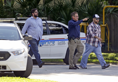 George Zimmerman, far right, is escorted to a home by a Lake Mary police officer, center, and Shawn Vincent, as assistant to his attorney, Monday, Sept. 9, 2013, in Lake Mary, Fla., after a domestic incident in the neighborhood where Zimmerman and his wife Shellie had lived during his murder trial. Zimmerman's wife says on a 911 call that her estranged husband punched her father in the nose, grabbed an iPad out of her hand and smashed it and threatened them both with a gun. Zimmerman was recently found not guilty for the 2012 shooting death of Trayvon Martin. (AP Photo/John Raoux)