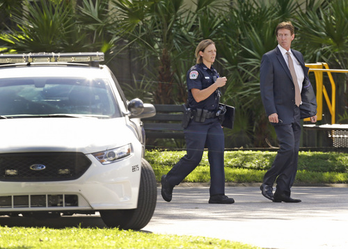 Mark O'Mara, attorney for George Zimmerman, speaks with a police officer at the scene of a domestic incident in the Lake Mary, Fla. neighborhood where Zimmerman and his wife Shellie had lived during his murder trial, Monday, Sept. 9, 2013. Zimmerman's wife says on a 911 call that her estranged husband punched her father in the nose, grabbed an iPad out of her hand and smashed it and threatened them both with a gun. Zimmerman was recently found not guilty for the 2012 shooting death of Trayvon Martin. (AP Photo/John Raoux)