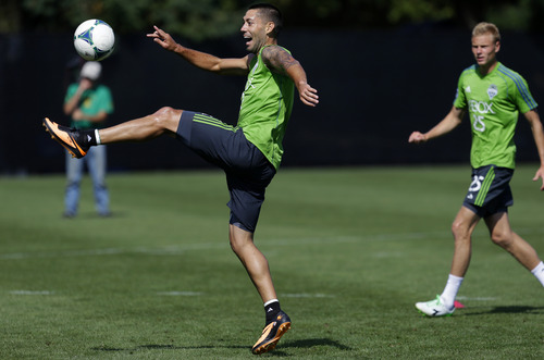 Clint Dempsey, left, the newest member of the Seattle Sounders FC MLS soccer team, trains for the first time with the team, Wednesday, Aug. 7, 2013, in Tukwila, Wash. At right is Andy Rose. The Sounders will face Toronto FC on Saturday. (AP Photo/Ted S. Warren)